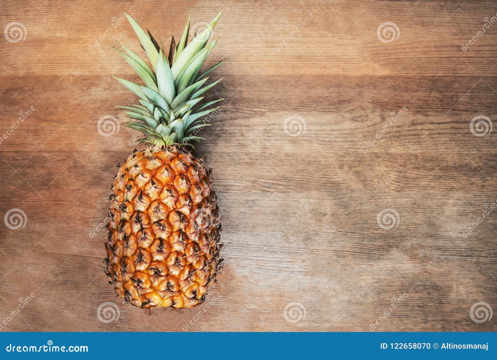 Singel en mycket hel organisk ananasfrukt på moget fullvuxet moget för träbakgrund, lagt ner på dess sida negativt tomt s
