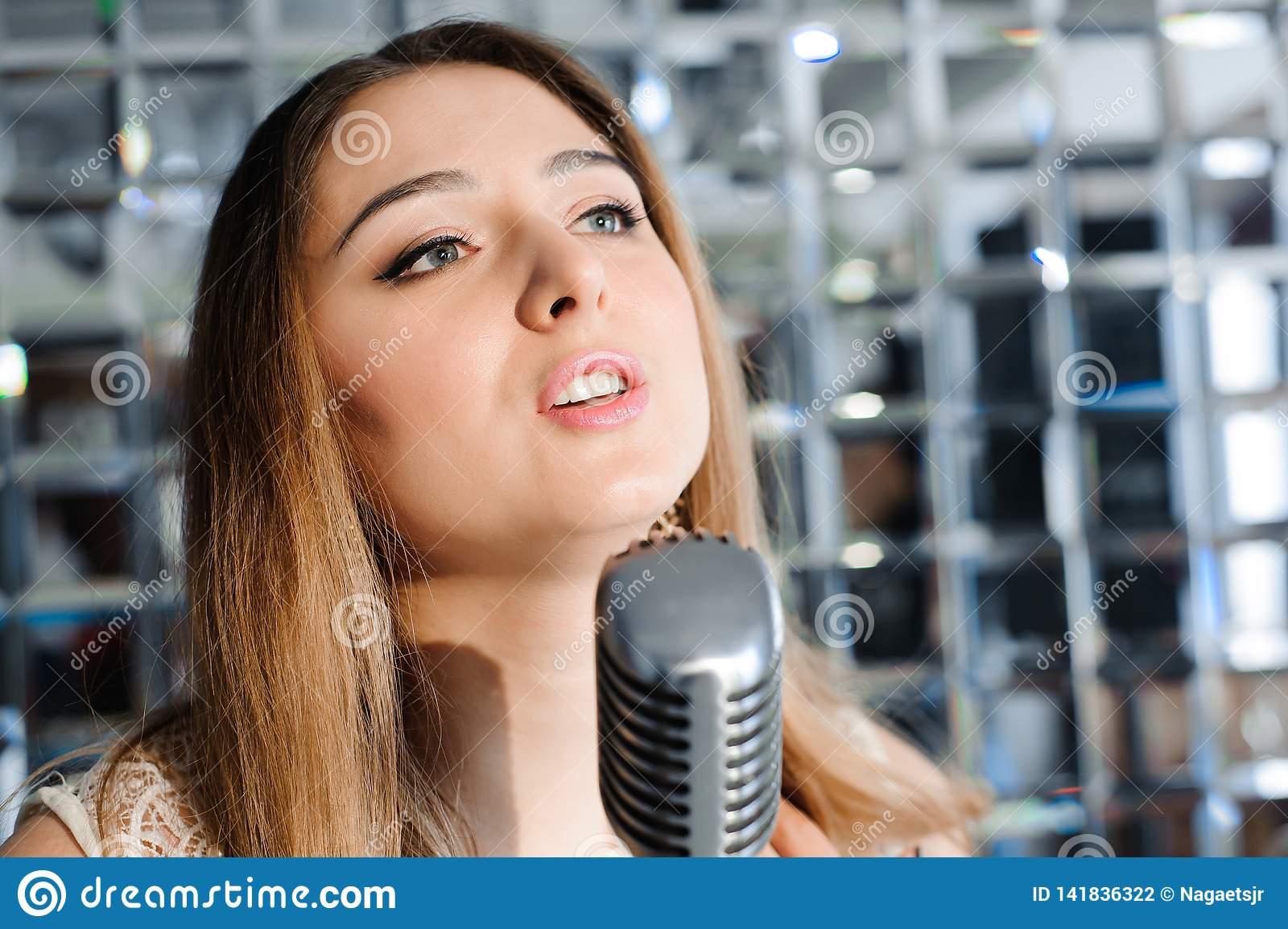 Singer in front of a microphone. beautiful woman singing on the stage next to the microphone.