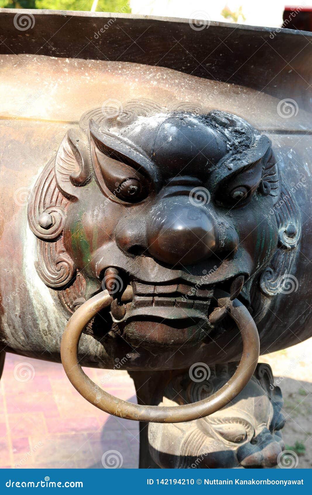 Singha statue on old joss stick pot ncense burner
