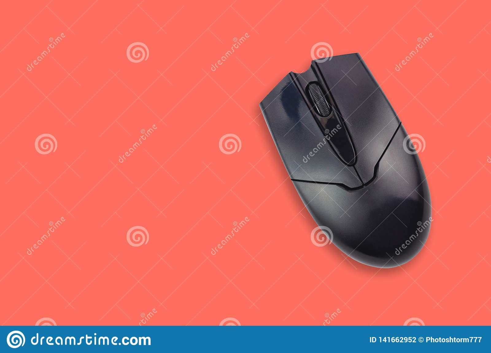 Single black plastic optical computer mouse on office table coral color. Top view. Copy space for your text
