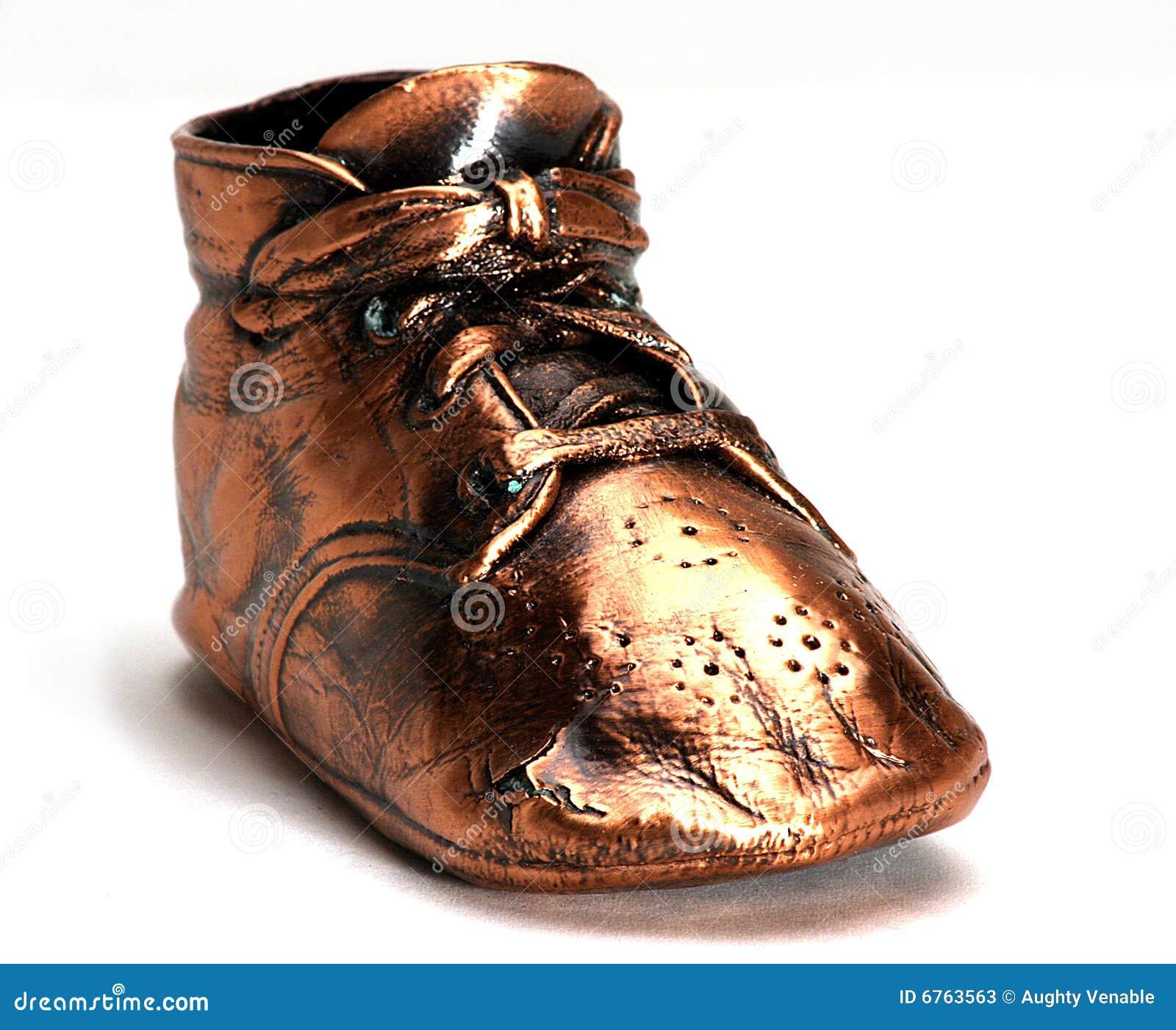Bronze baby shoe on white background