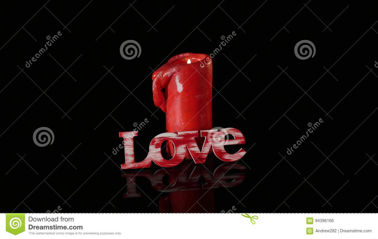 A single burning red candle rotate in front of black background