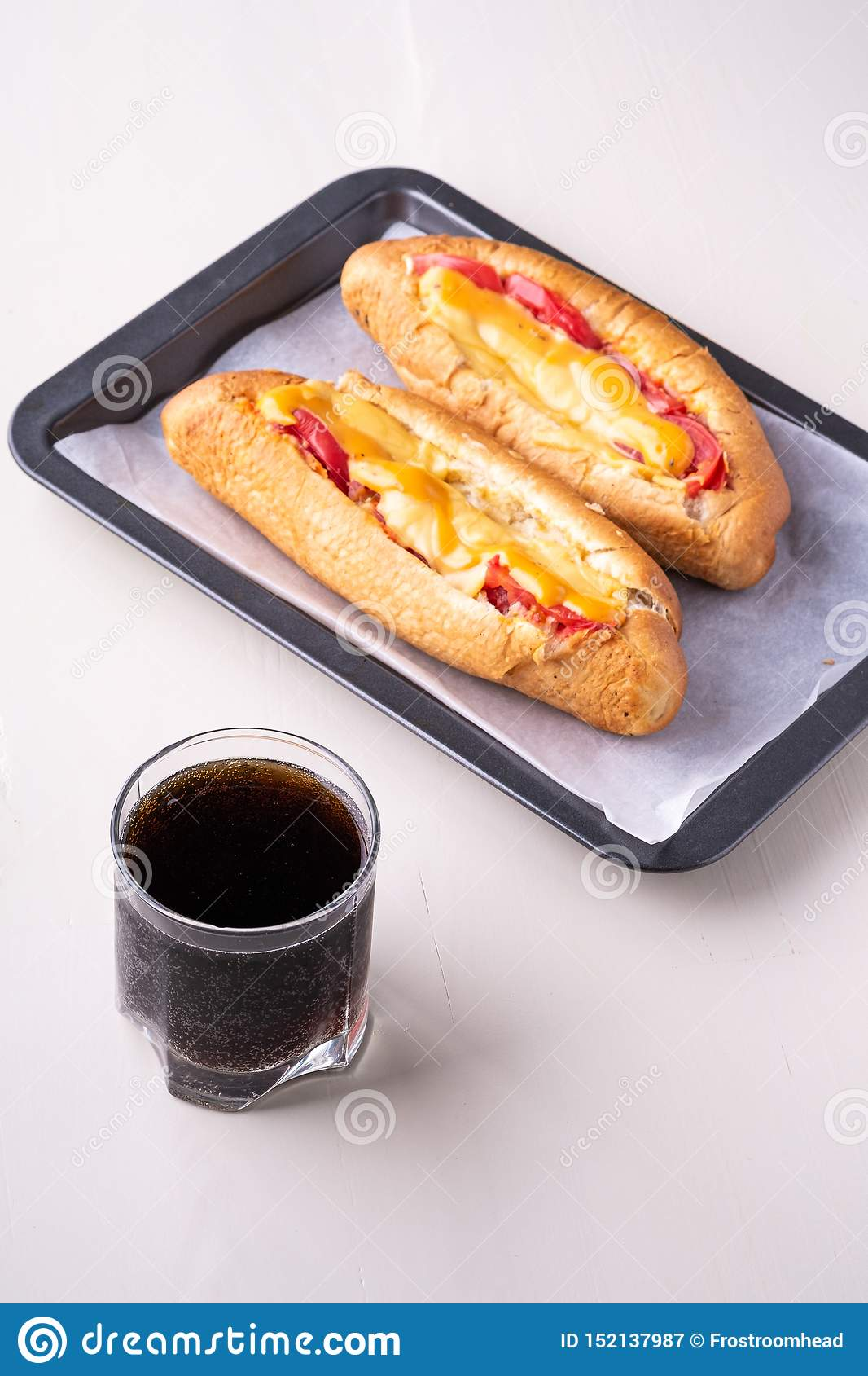 Single glass of cola drink with two hot dog fast food junk fresh sausage cheese sauce isolated on baking tray white background
