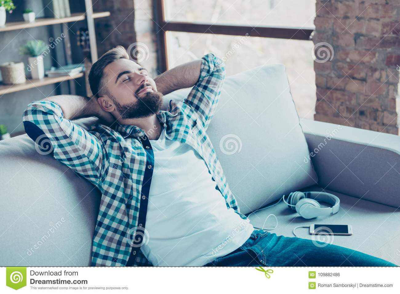 Single, happy young man in checkered shirt is relaxing on the so