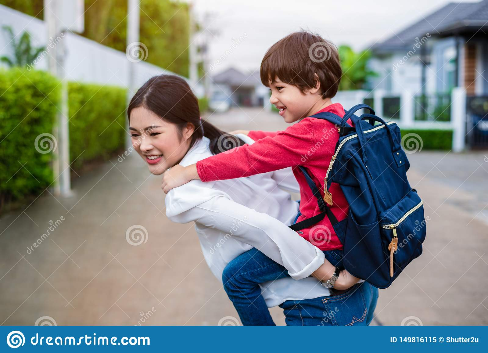 Single mom carrying and playing with her children near home with villa street background. People and Lifestyles concept. Happy