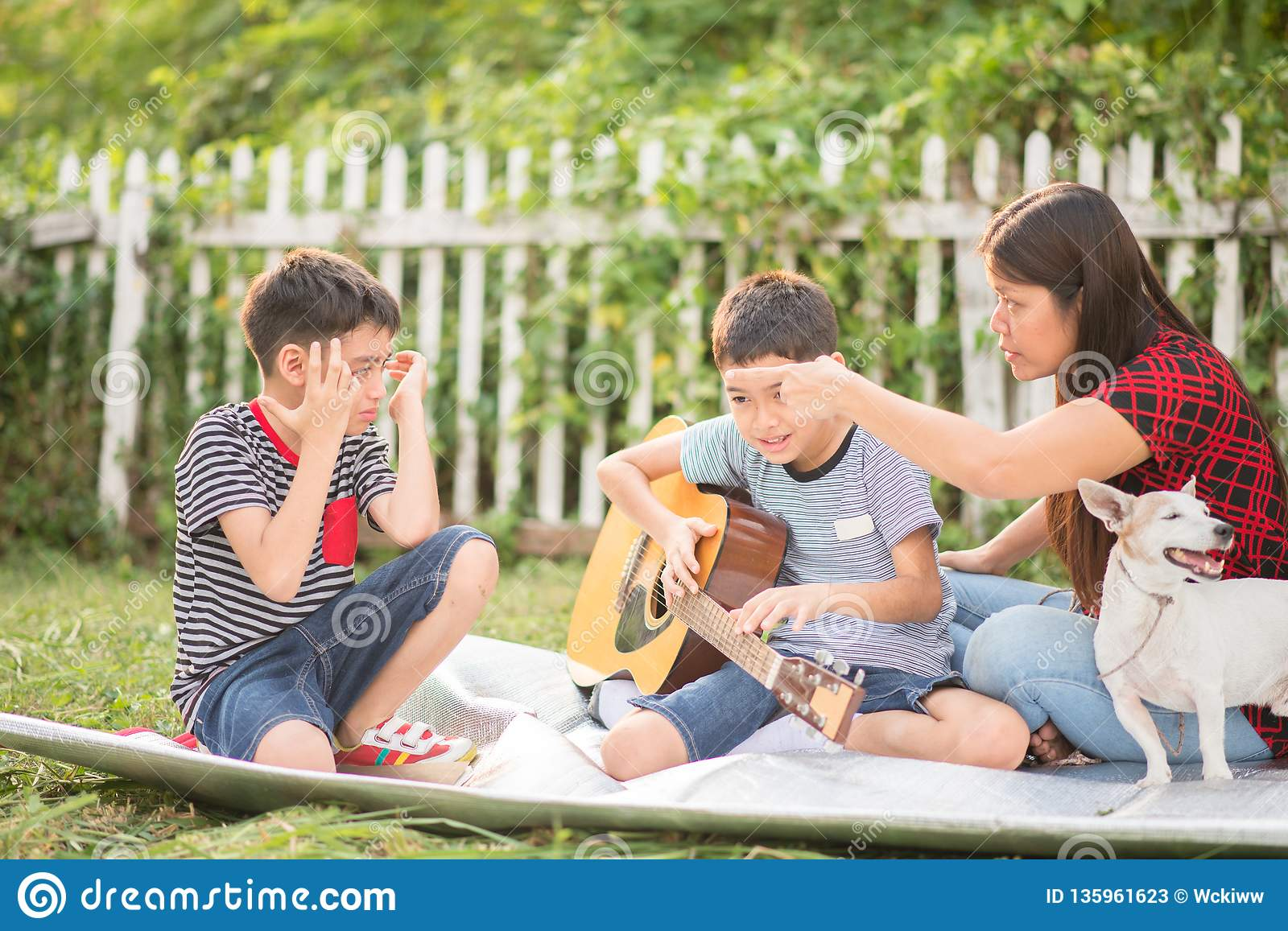 Single mom and sons play guitar together in the park