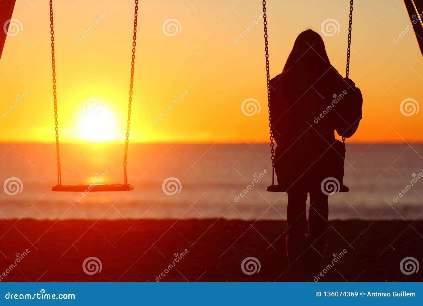 Single woman sitting on a swing contemplating sunset