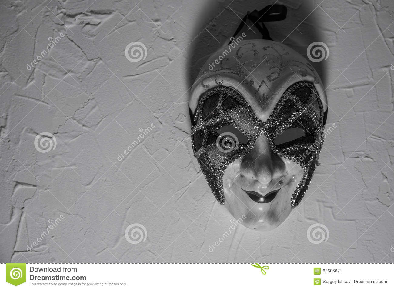 Sinister joker mask on white wall