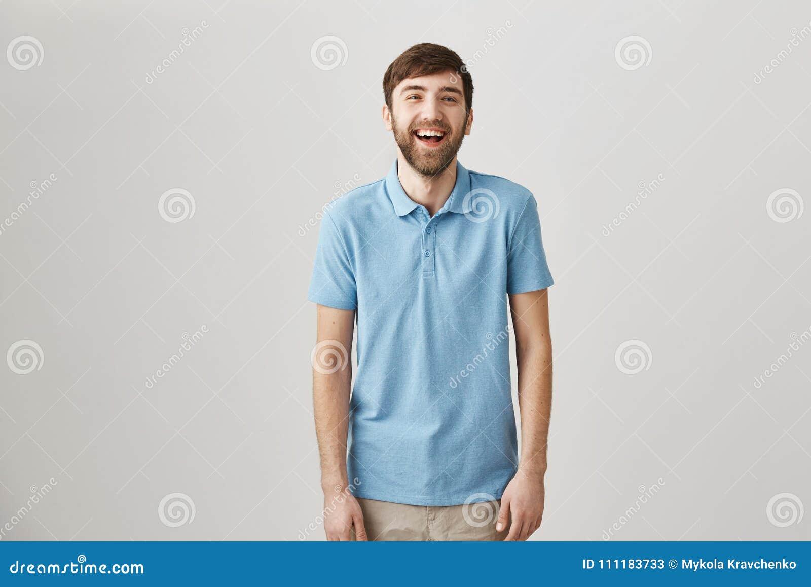 Sinne för humor gör mannen unik Stående av den spensliga vanliga caucasian grabben med skägget och mustaschen som skrattar och