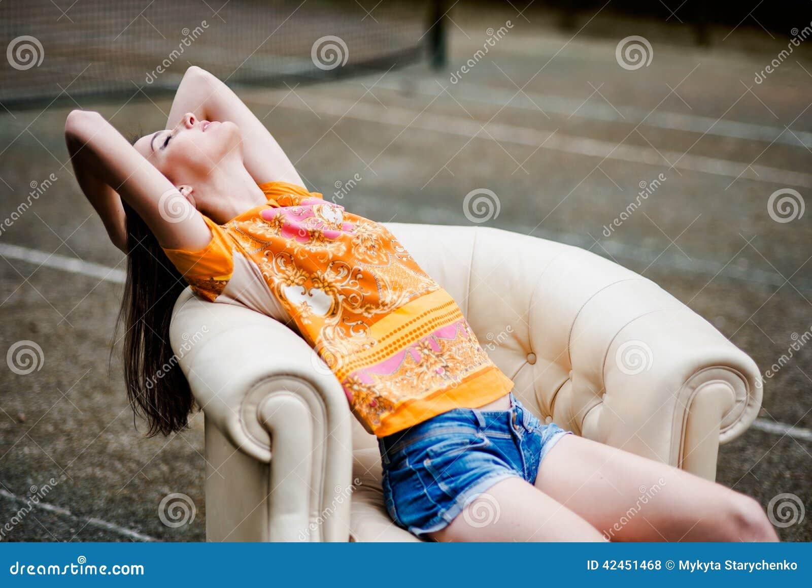 Sinnliche elegante junge Frau, die auf weißer Ledercouch sich entspannt