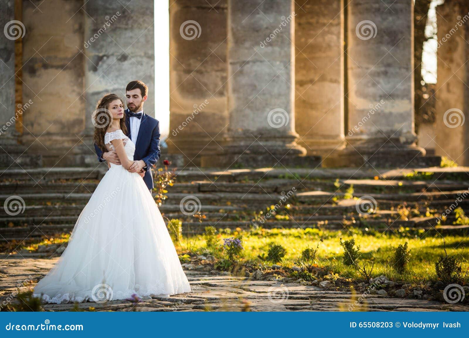 Sinnliche romantische Jungvermähltenbraut und -bräutigam, die vor alter barocker Kirche umarmt