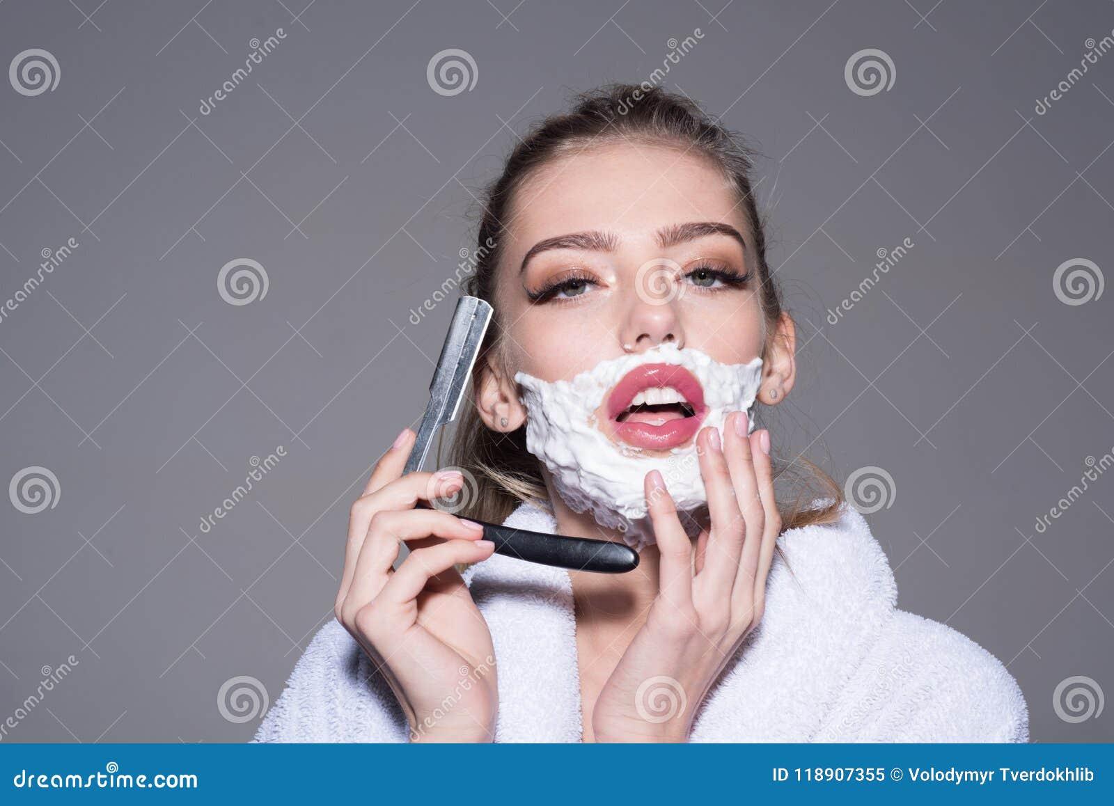 8201d55d09752f Sinnliches blondes Mädchen im weißen Bademantel, der  Schnittkehlrasiermesser in ihren Händen lokalisiert auf grauem Hintergrund