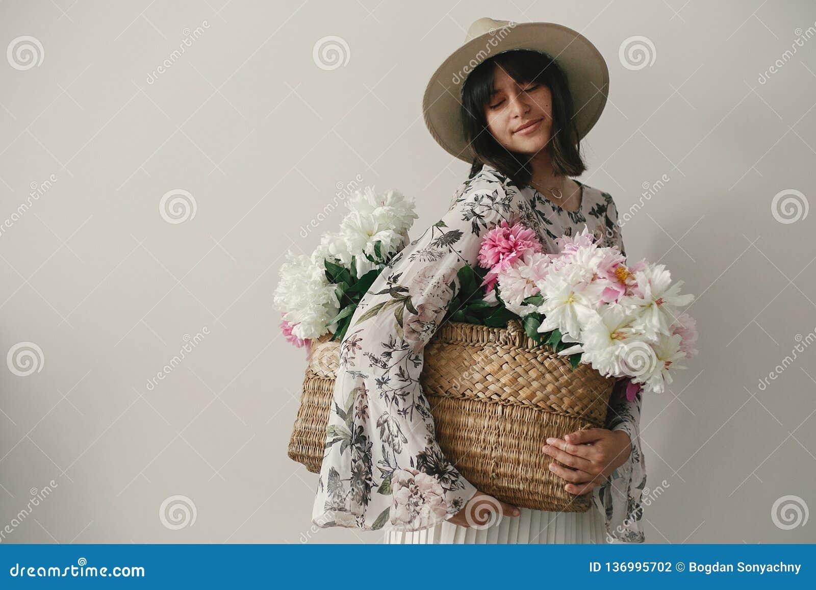 Sinnliches Porträt von boho Mädchen die Rosa- und weißepfingstrosen im rustikalen Korb halten Stilvolle Hippie-Frau im Hut und in