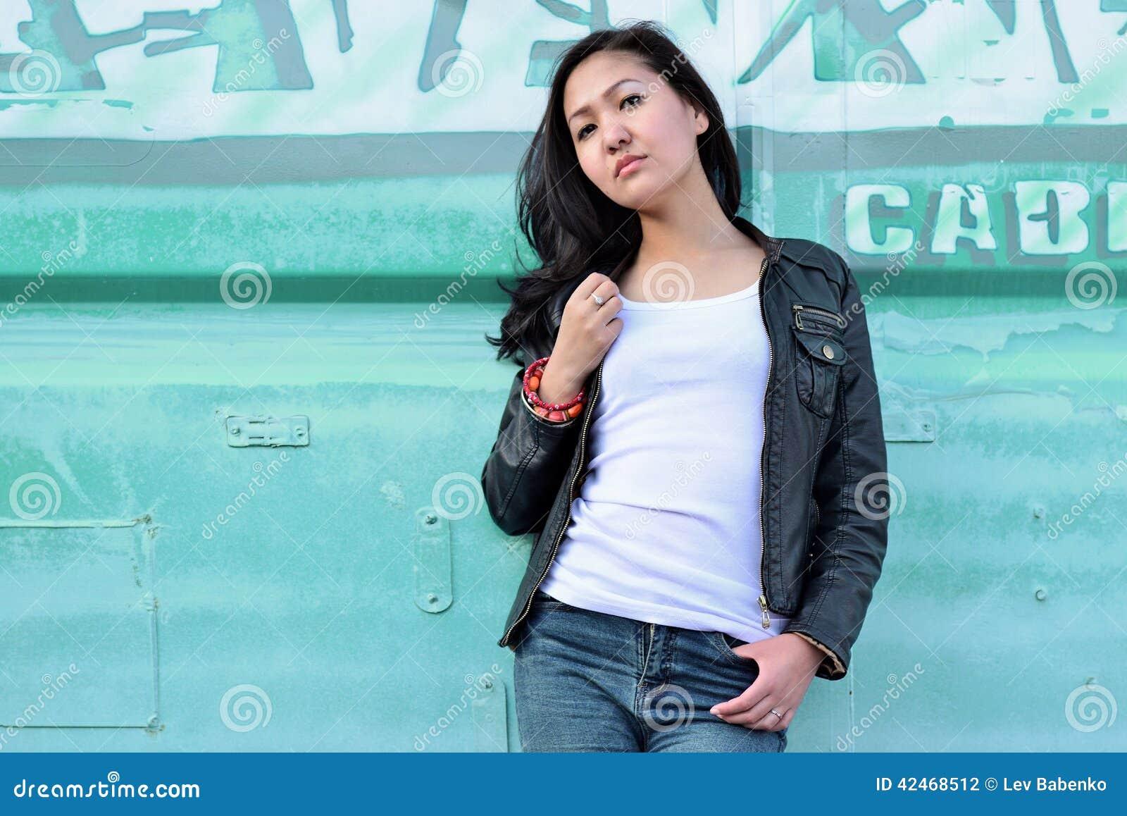 Sinnlichkeitsfrau im weißen T-Shirt, in der schwarzen Lederjacke, in den Blue Jeans und im schwarzen langen Haar im blauen städti