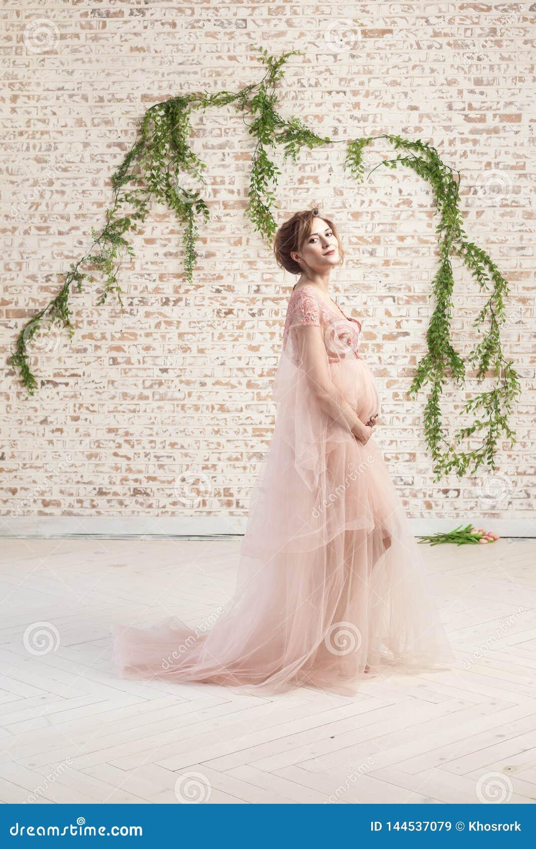 Sinnlig gladlynt härlig gravid ung kvinna, i rosa anseende och att rymma för klänning med förälskelse hennes buk