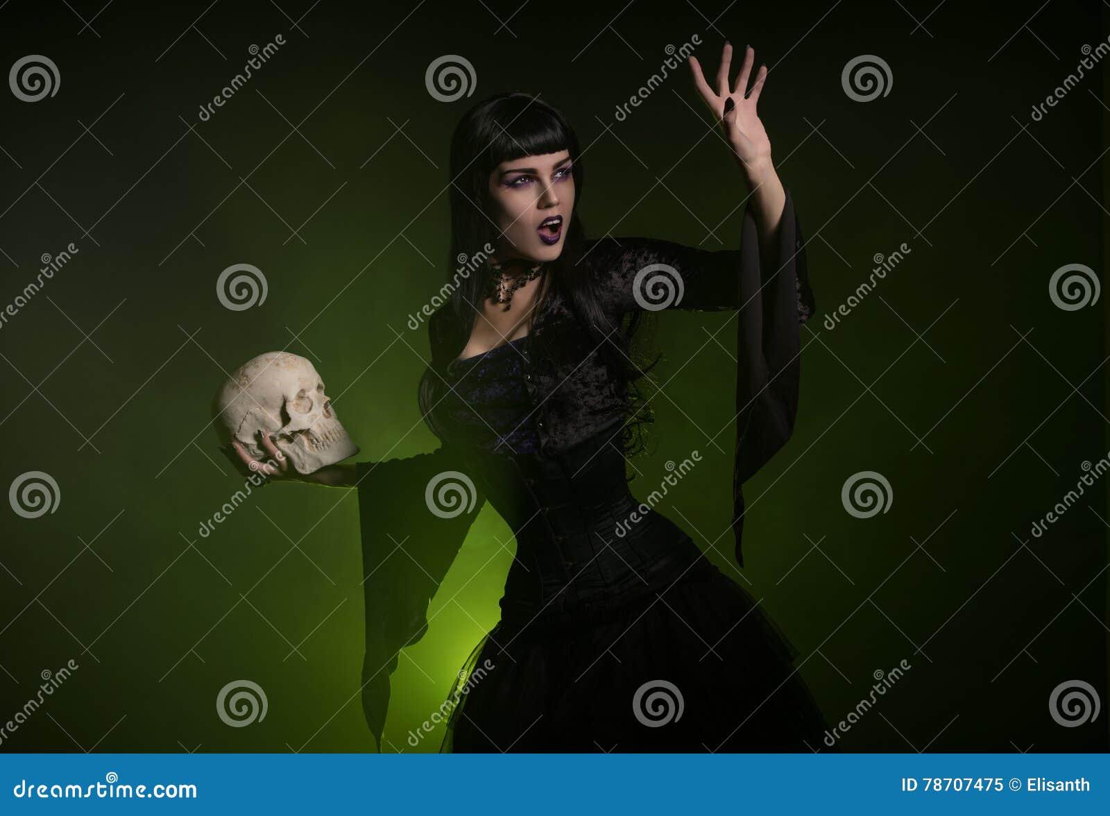 Sinnlig häxa som rymmer en skalle i hennes hand