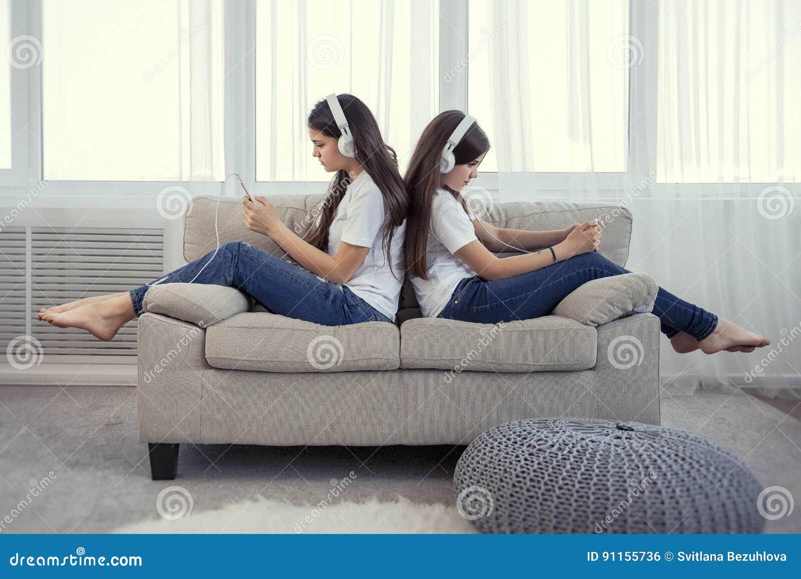 Siostr nastoletnie dziewczyny z słucha muzykę, ommunicate w ogólnospołecznych sieciach i