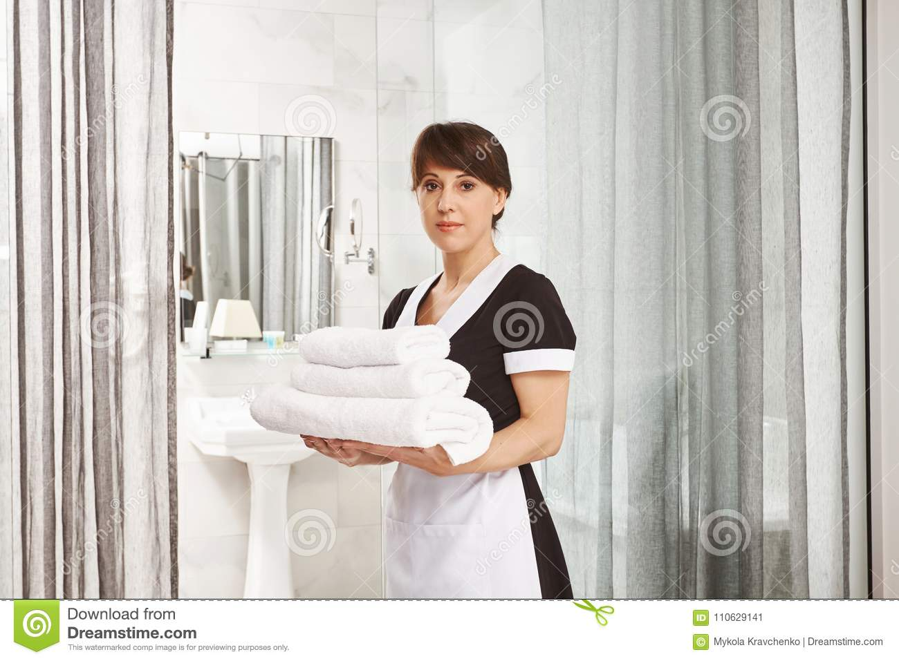 Sir, I will put extra towels in bathroom. Portrait of woman in maid uniform standing with white hotel towels near door