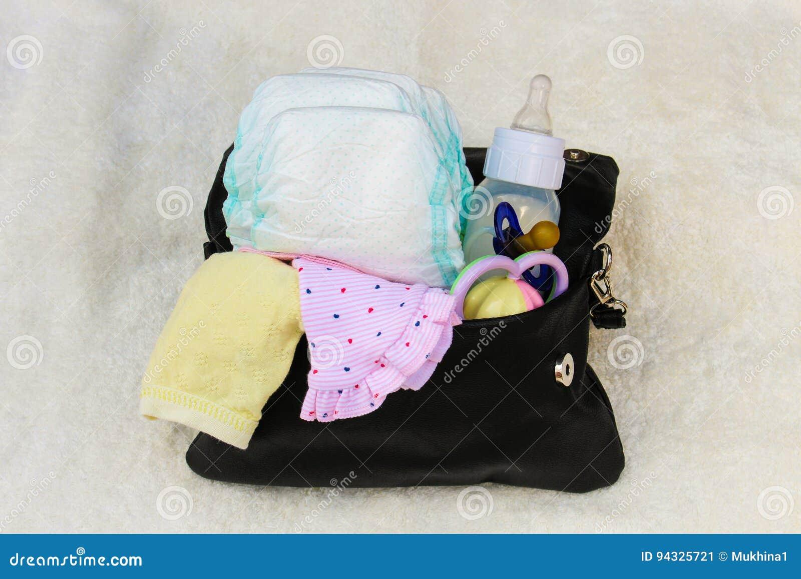 Sira de mãe à bolsa do ` s com artigos para importar-se com a criança