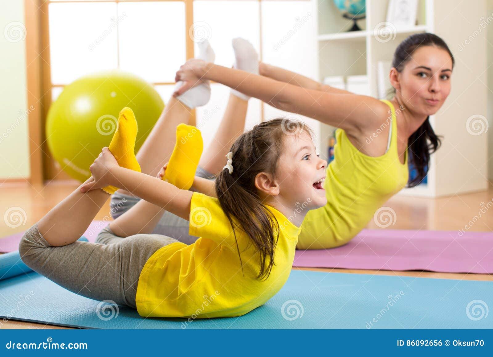 Sira de mãe e caçoe no centro do gym que faz esticando o exercício da aptidão yoga