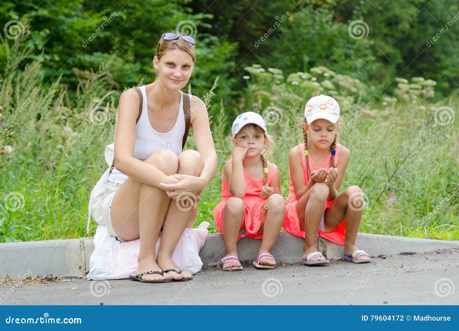 Sira de mãe e duas crianças que sentam-se no freio da estrada que espera o ônibus