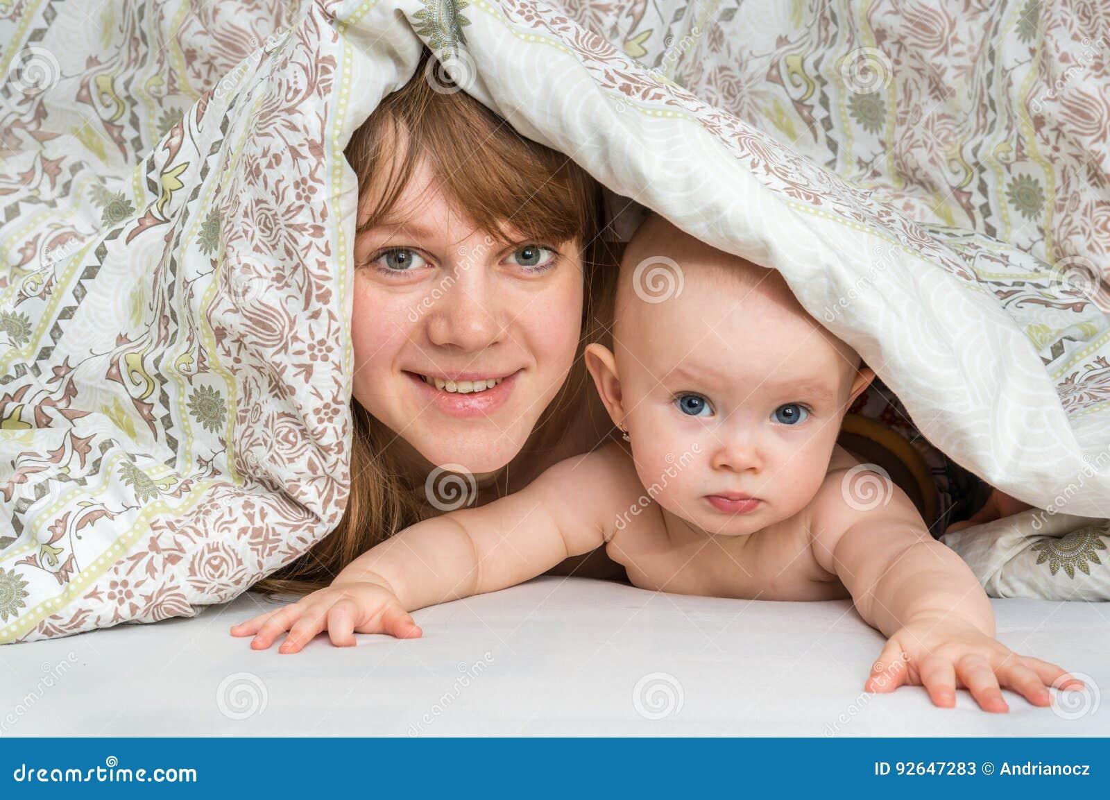 Sira de mãe e seu bebê que joga e que sorri sob uma cobertura