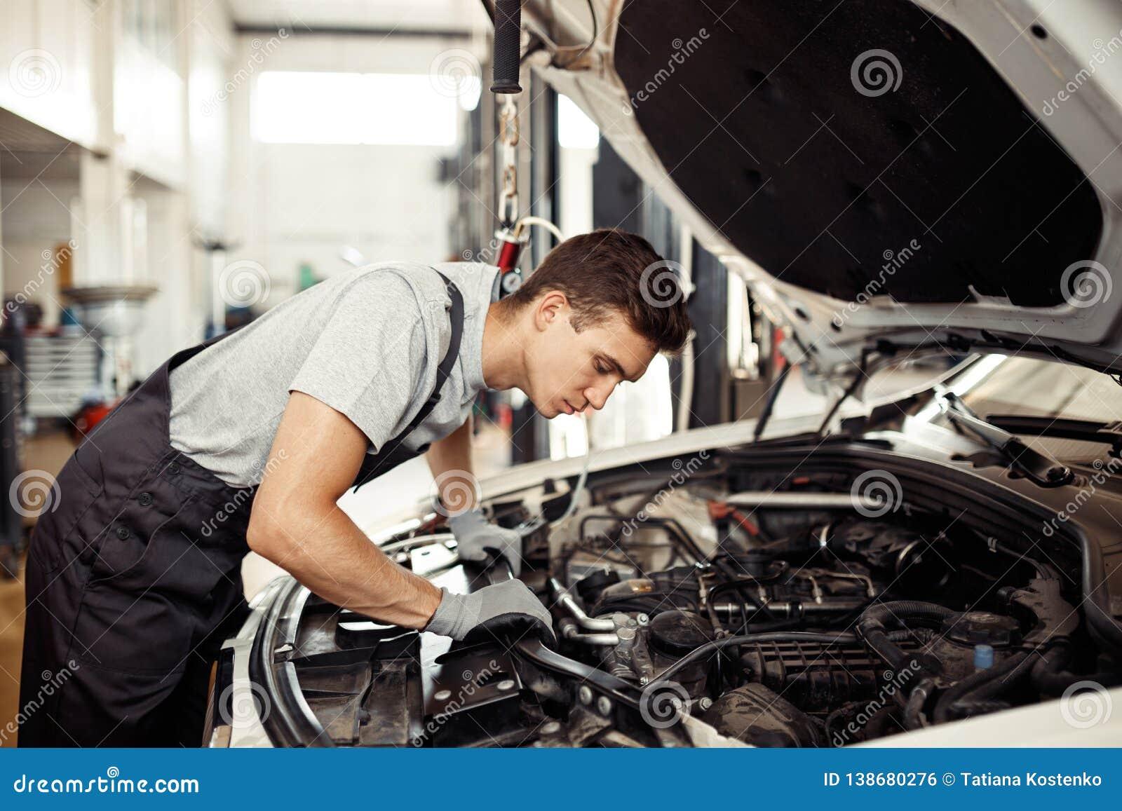 Sirst da segurança: um mecânico de carro bonito está verificando o motor