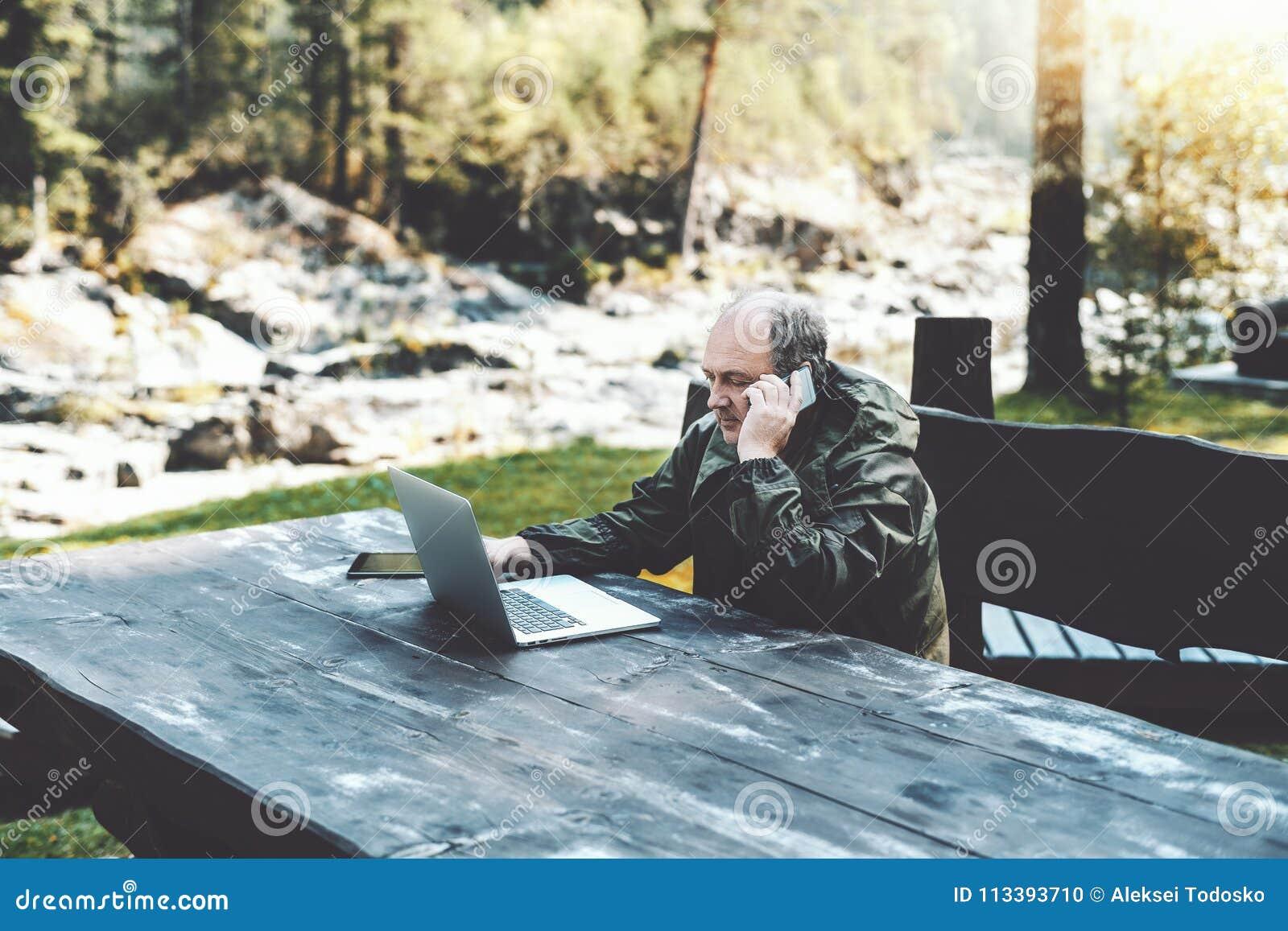 Sirva al empresario con el ordenador portátil que habla en el teléfono en bosque
