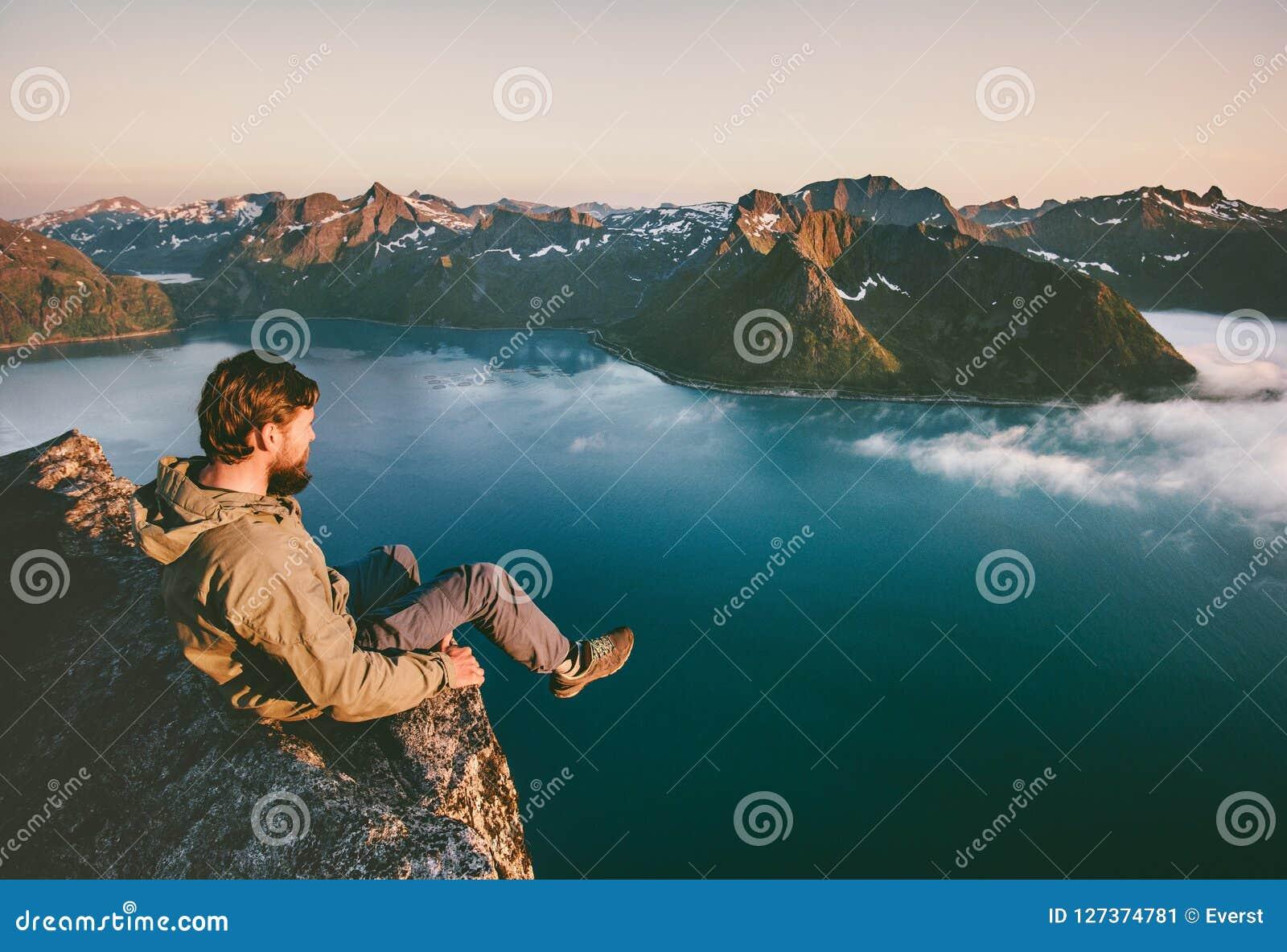 Sirva al turista que se sienta solamente en las montañas del acantilado del borde sobre el mar