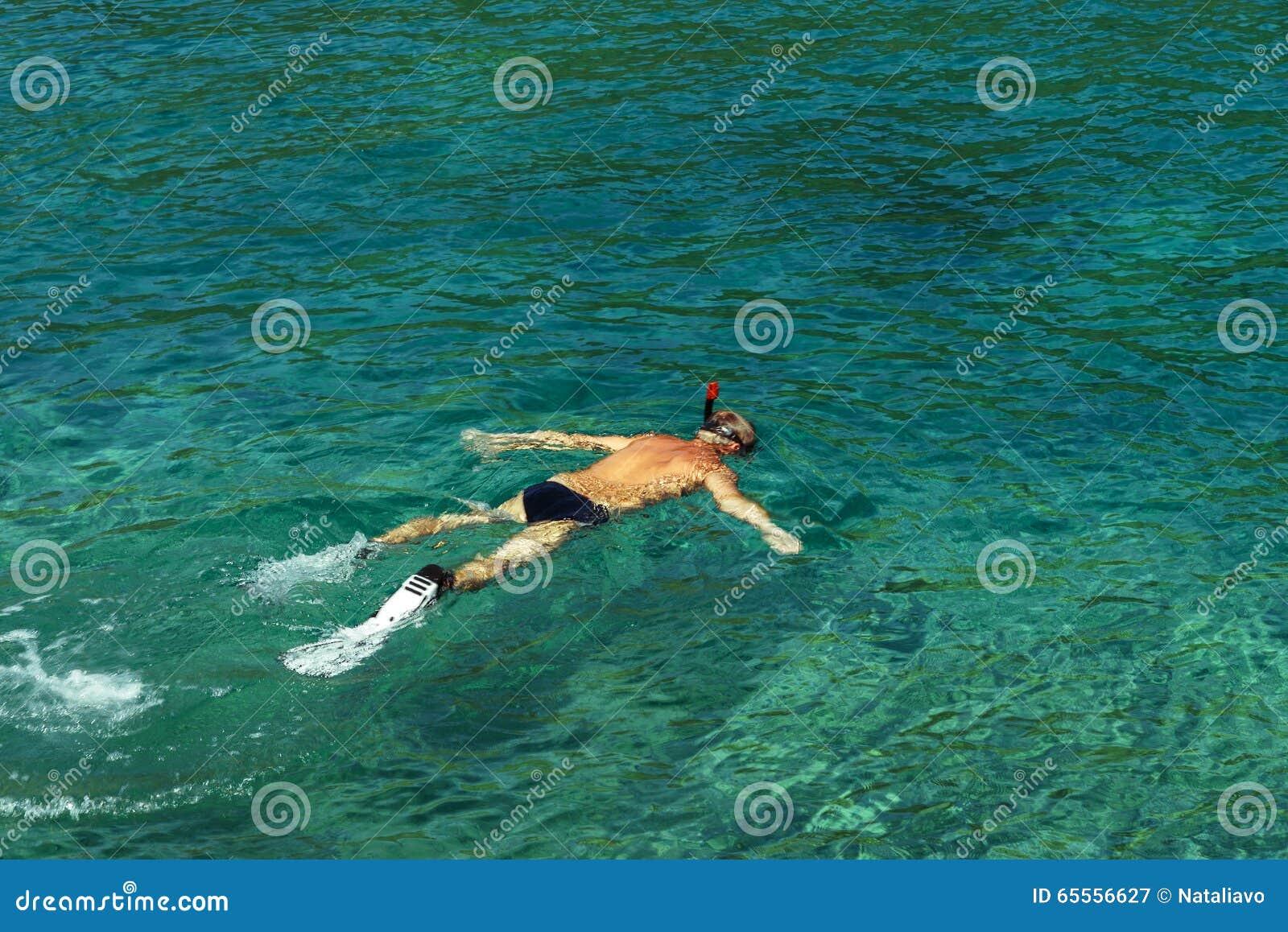 Sirva bucear con las aletas, la máscara y el snorke en el lazure, agua de mar clara del mar adriático Manchas de la luz del sol e