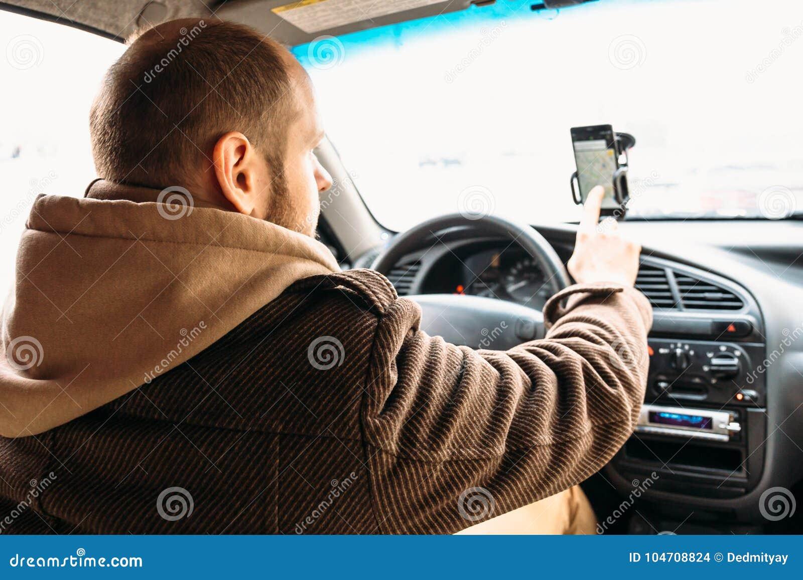 Sirva el conductor en el coche que toca a mano la pantalla del smartphone con el sistema de navegación del uso