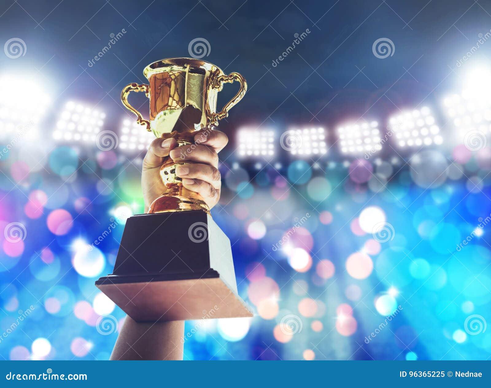 Sirva el soporte una taza del trofeo del oro, concepto del triunfo