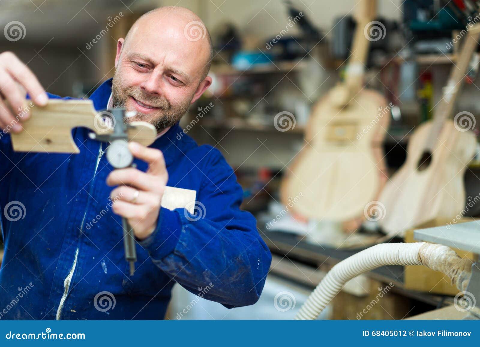 Sirva el trabajo en una máquina en el taller de la guitarra