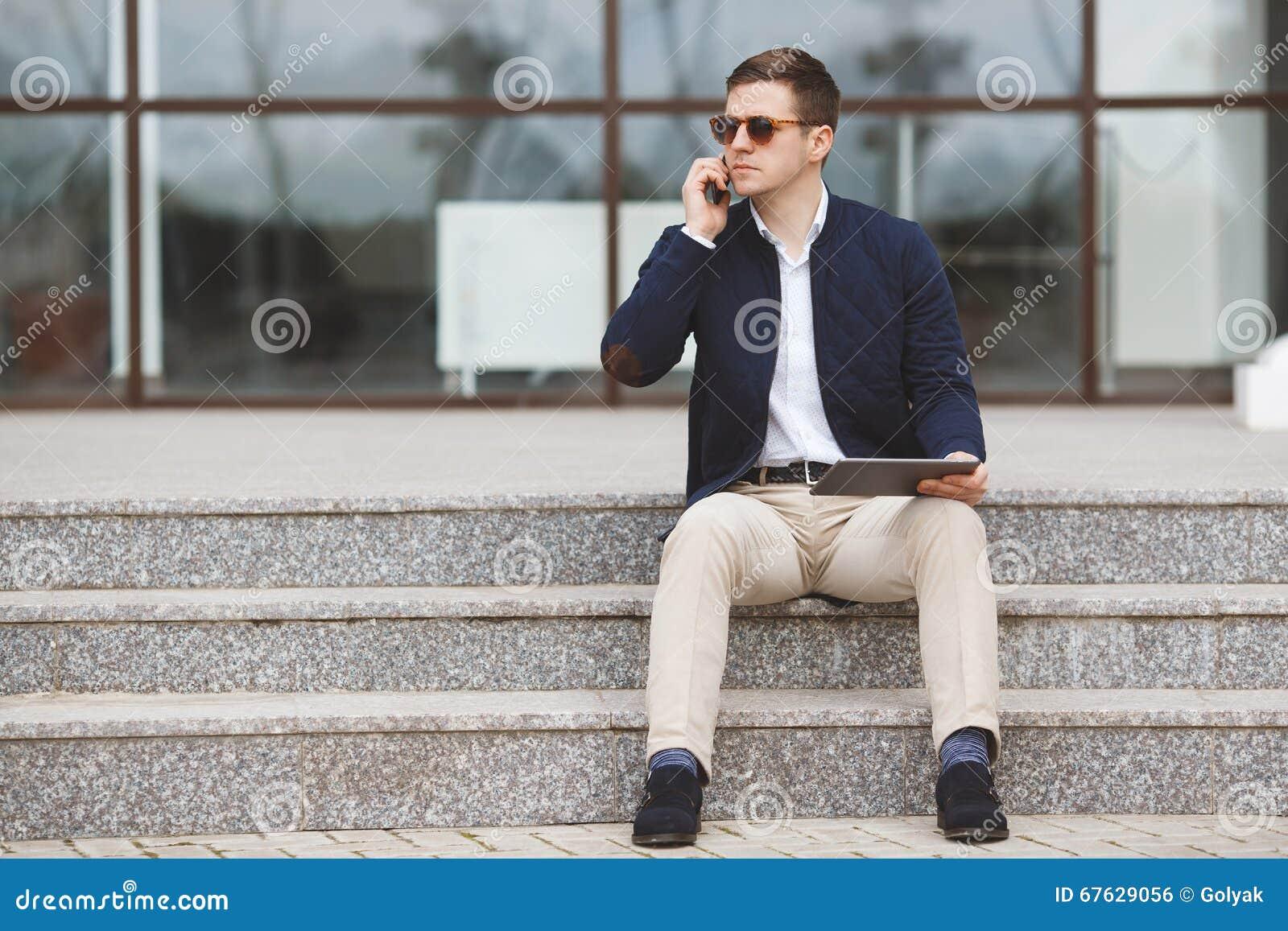 Sirva hablar en el teléfono que se sienta en las escaleras