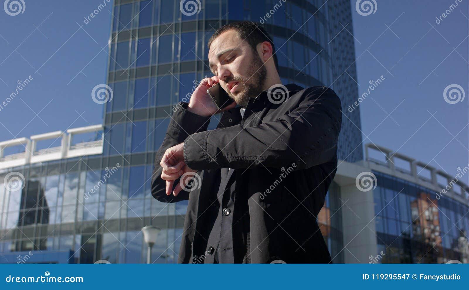 Sirva hablar en el teléfono y la mirada en su reloj al aire libre