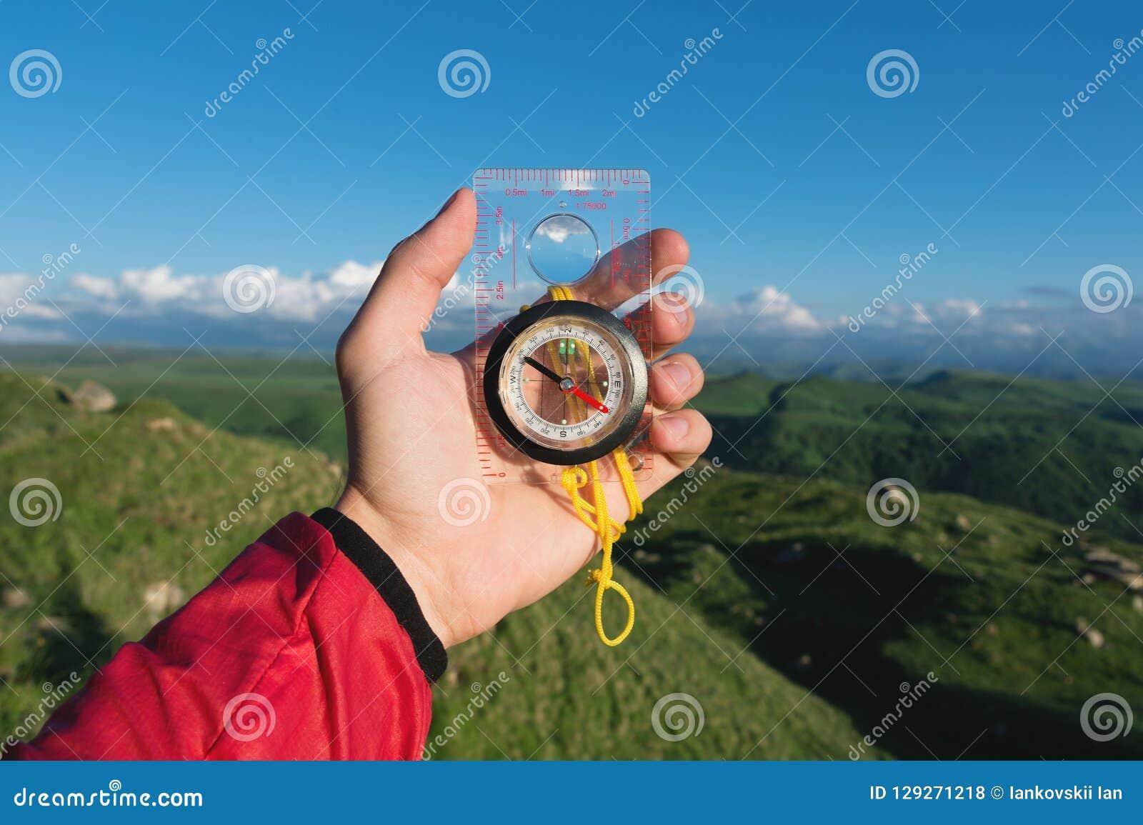 Sirva la búsqueda de la dirección con un compás en su mano en el punto de vista de las montañas del verano Búsqueda de la direcci
