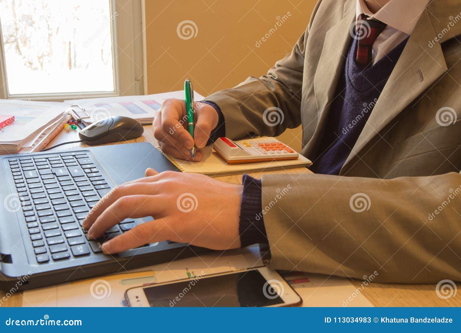 Sirva la mano con la pluma, la calculadora y el ordenador en la tabla de madera