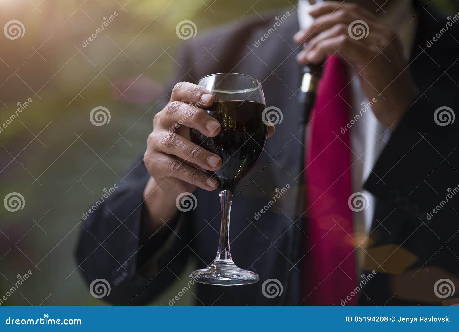 Sirva la mano del ` s con un vidrio de vino rojo