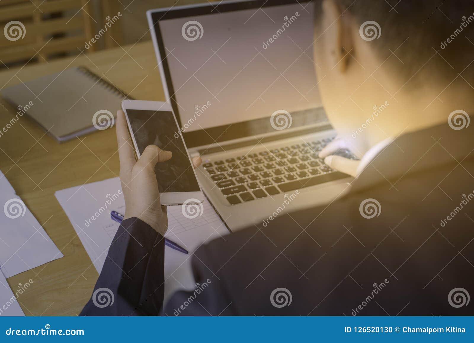 Sirva la mano usando el teléfono móvil con el ordenador portátil en la tabla de madera con la hoja
