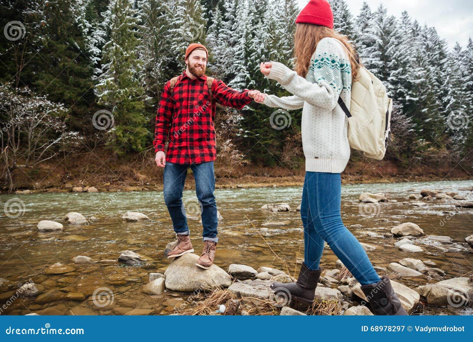Sirva a la mujer de ayuda para caminar en las rocas