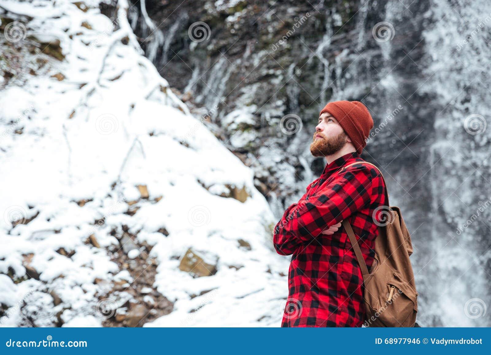 Sirva la situación con los brazos cruzó cerca de la cascada de la montaña en invierno