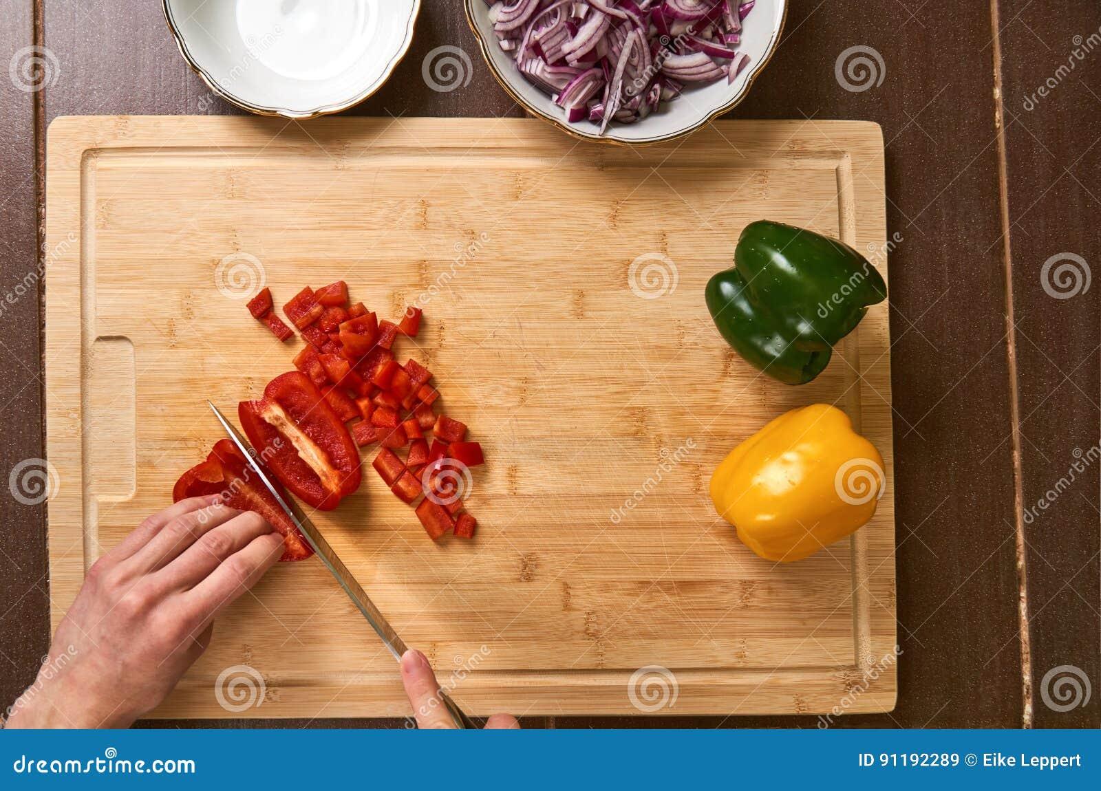 Sirva las manos del ` s que cortan verduras frescas en la cocina, preparando una comida para el almuerzo El top abajo ve
