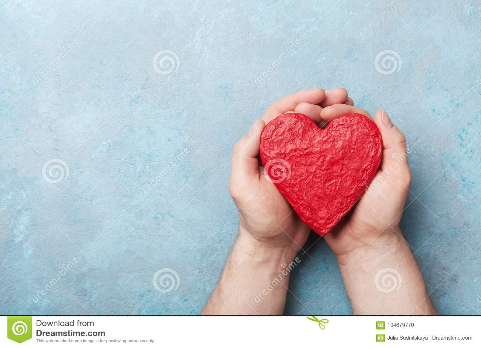 Sirva llevar a cabo un corazón rojo en la opinión superior de las manos Concepto sano, del amor, del órgano de la donación, del d
