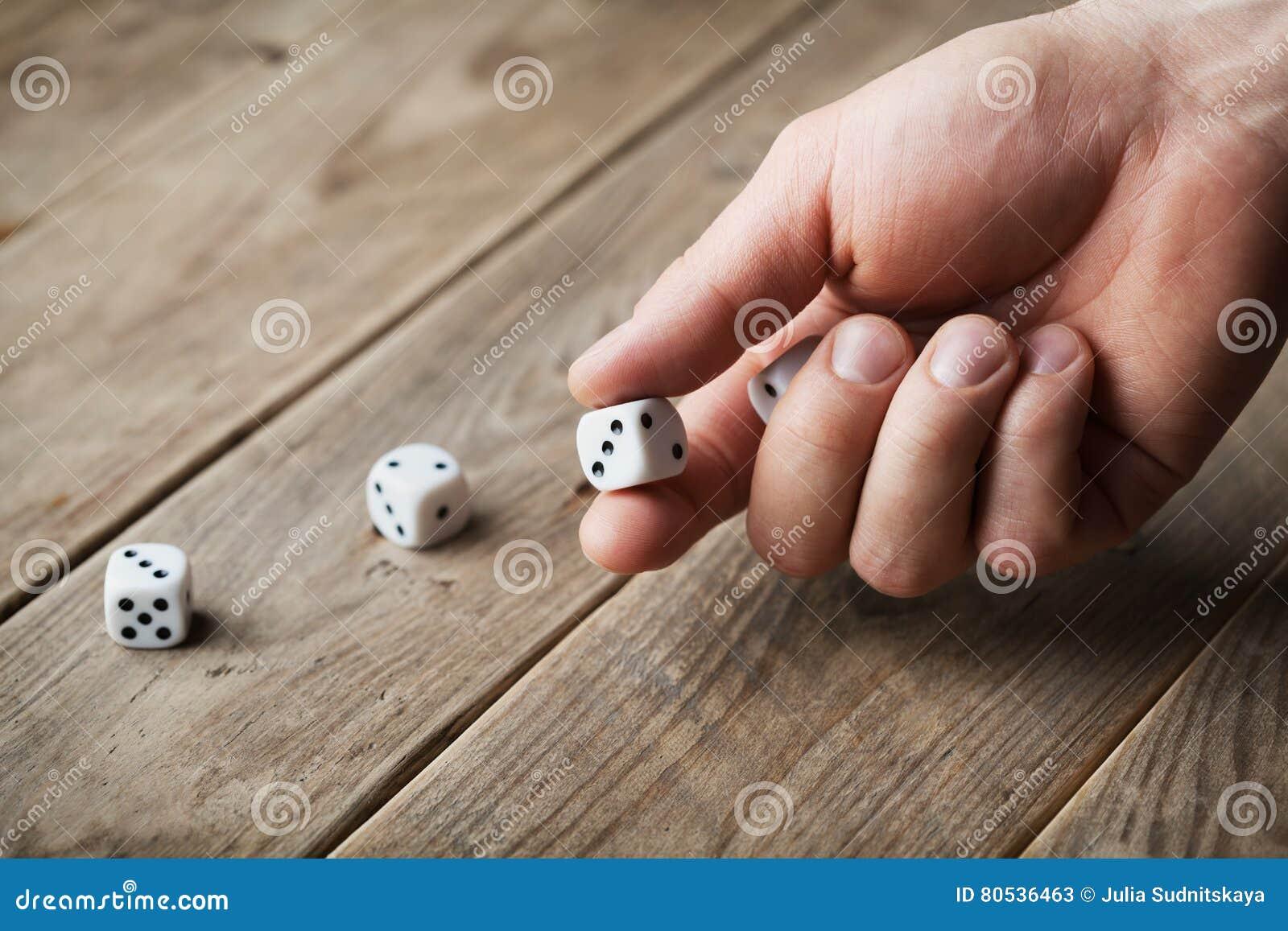 Sirva los dados blancos que lanzan de la mano en la tabla de madera Dispositivos de juego Juego del concepto de azar