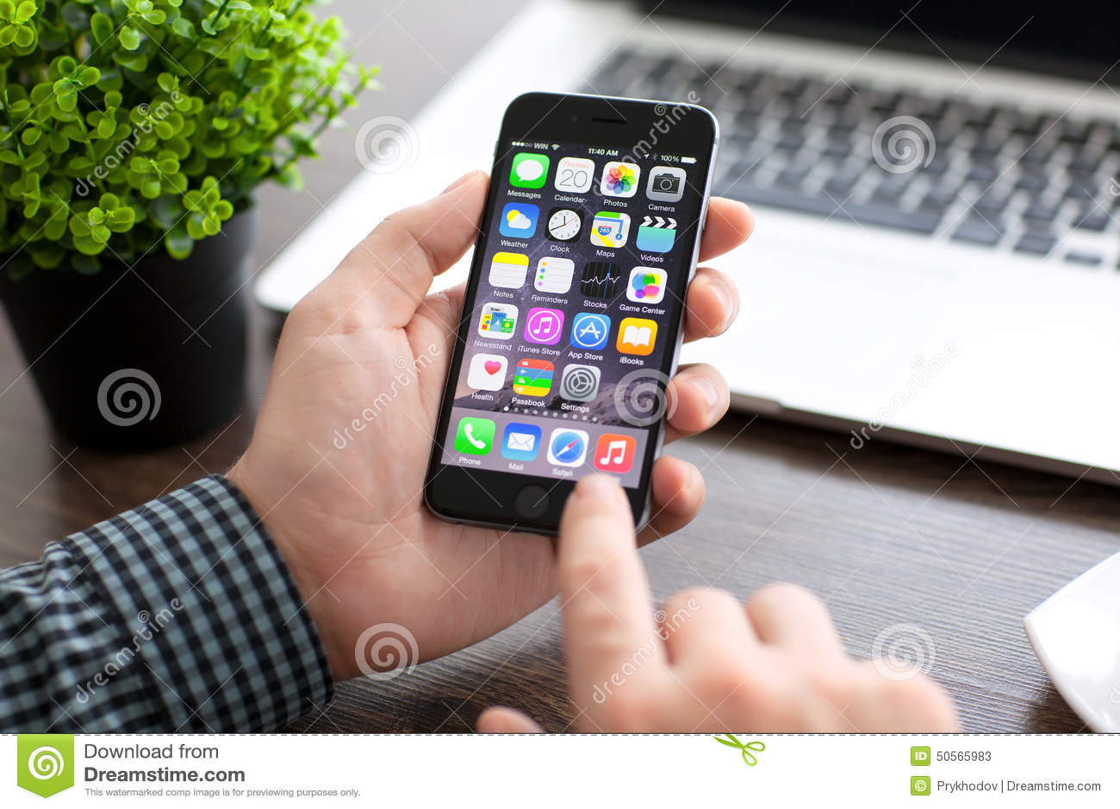 Sirva sostener el iPhone 6 del teléfono sobre la tabla con Macbook