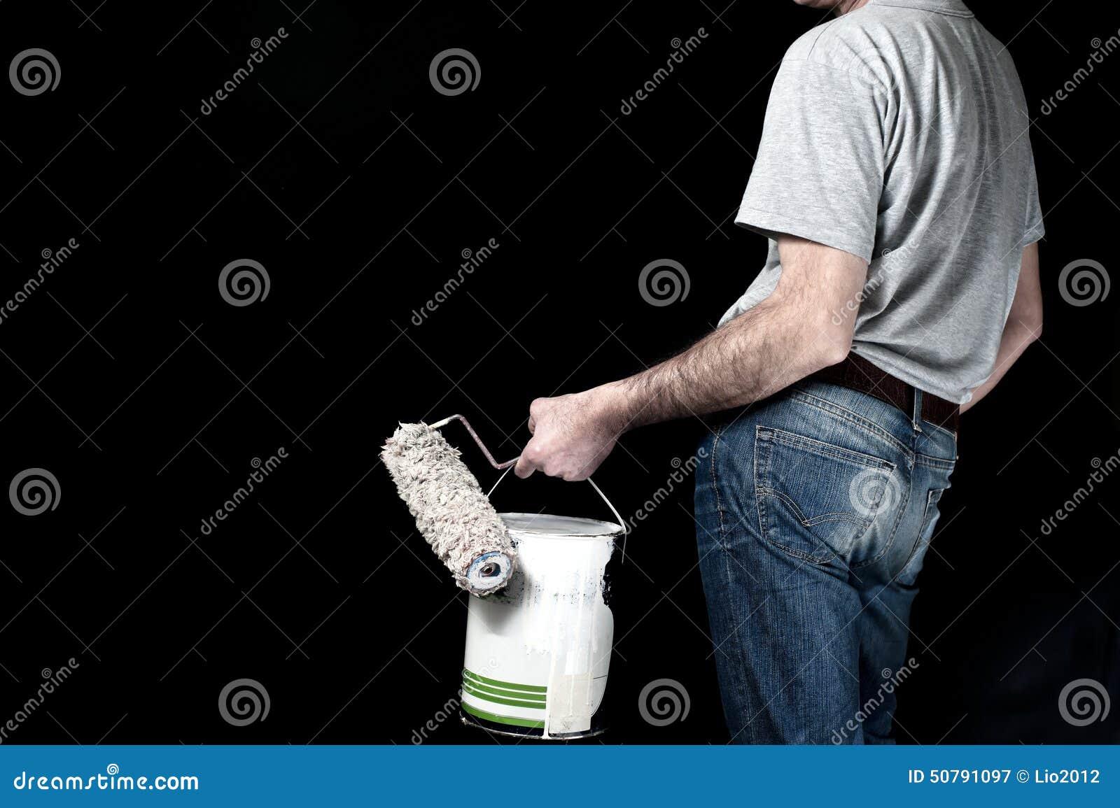 Sirva sostener el rodillo de pintura y un cubo de pintura