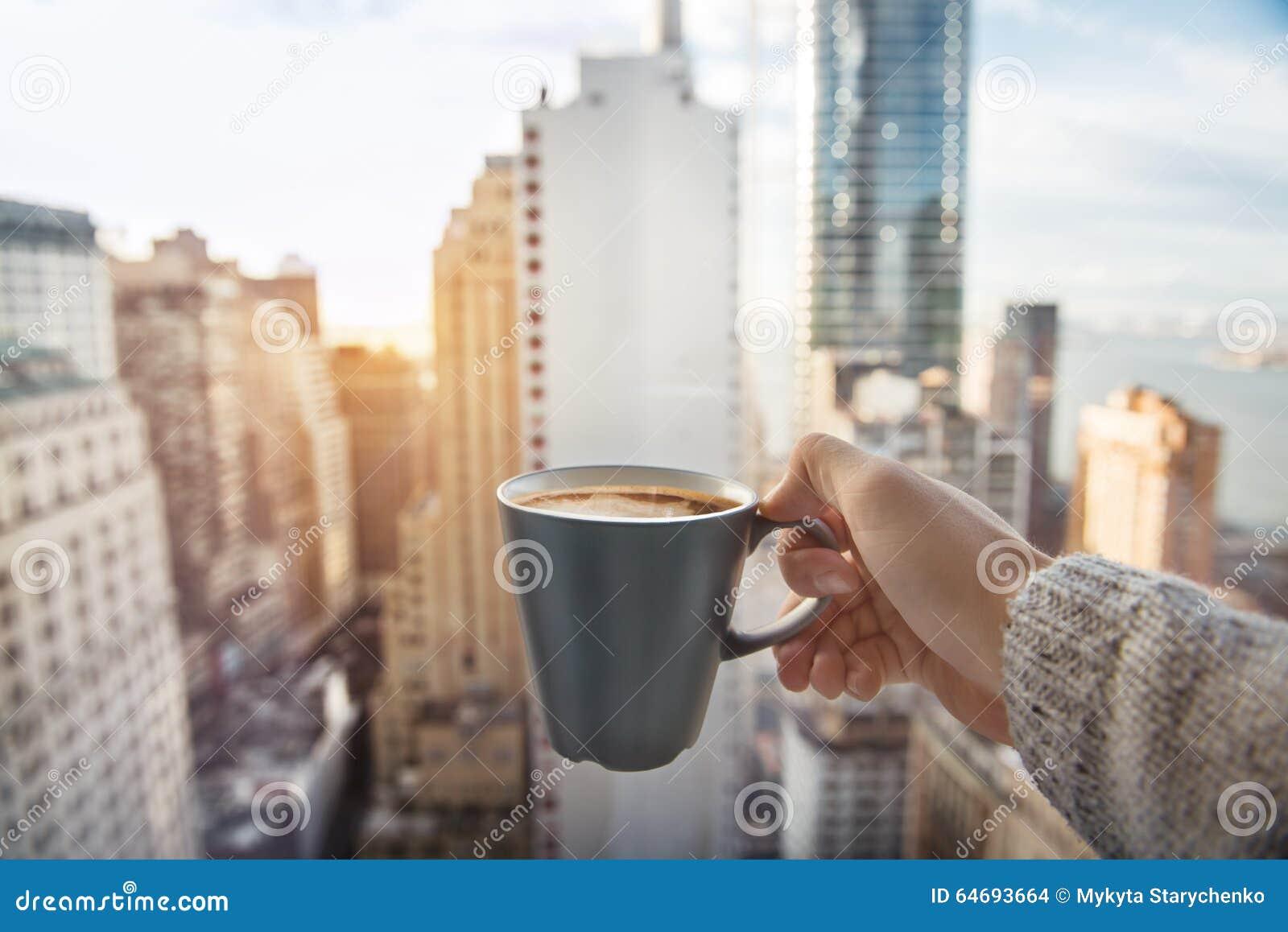 Sirva sostener la taza de café en apartamentos de lujo del ático con la visión a New York City