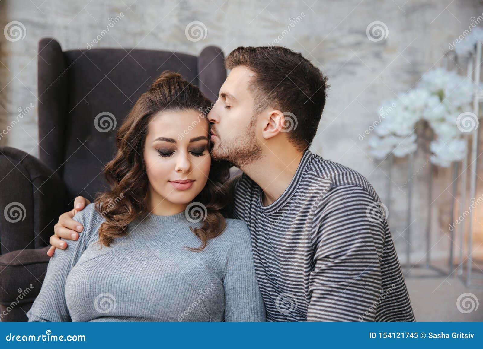 Sist novo da fam?lia perto da cadeira e olhar na barriga Mulher de Pregman com seu homem amado Pares felizes
