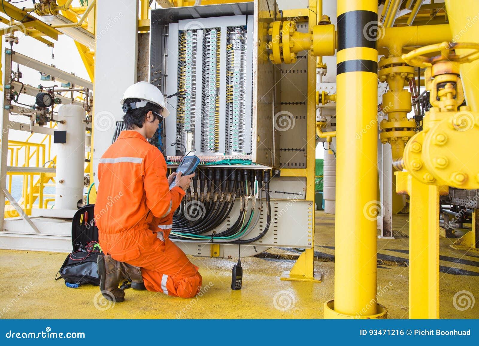 Sistema bonde bonde e do instrumento do técnico da manutenção no petróleo e gás a pouca distância do mar que processa a plataform