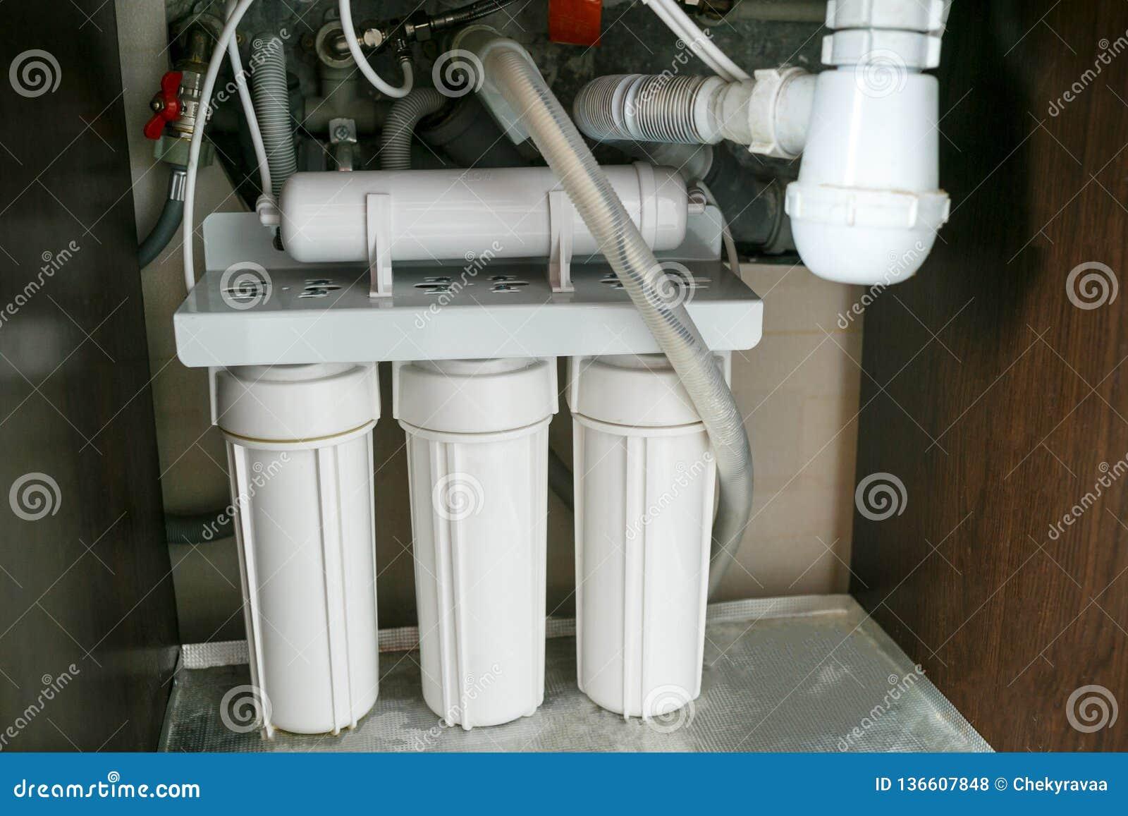 Sistema da purificação de água da osmose reversa em casa A instalação de filtros da purificação de água sob a banca da cozinha no